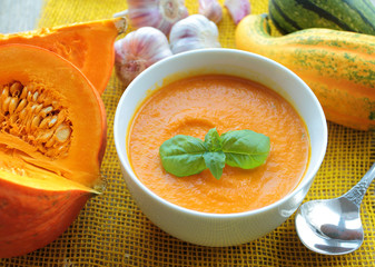 Bowl with pumpkin cream soup with basil