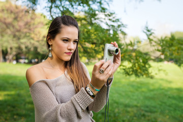 Portrait of young woman with compact camera outdoors in a park.