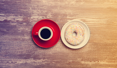 Cup of coffee and donut on a table.