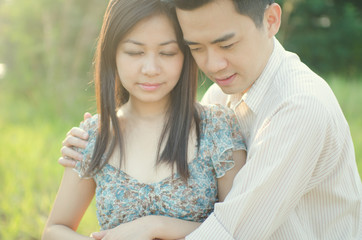 chinese young couple embracing each other on meadow