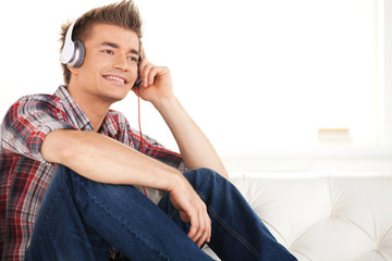 Happy man in headphones relaxing on sofa at home.