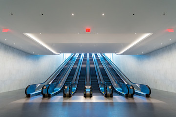 Futuristic escalator with blue light coming from upstairs