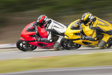 Two motorcycle leaning into a fast corner on track