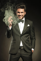 Happy business man holding a smoking cigarette in his hand.
