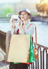 Beautiful girl with shopping bags taken picture of herself