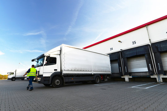 Unloading cargo trucks at warehouse building