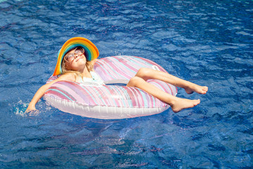 little girl  lying on the  inflatable rubber circle  in the swim
