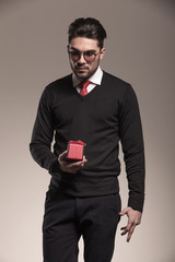 Attractive business man holding a small red gift