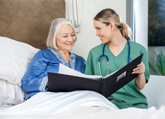 Caregiver Showing Medical Reports To Senior Woman