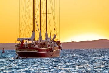 Old wooden sailboat at golden sunset