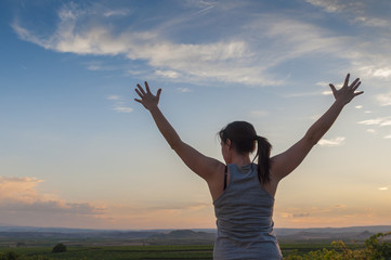 Young woman, hands up, sowing happiness at sunset