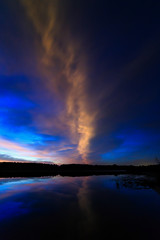 Cloud in the sky lit morning dawn, reflected in the water of the
