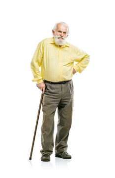 Old bearded man walking with cane