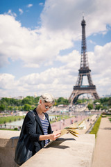 Young blonde woman looking at map of the city in front of the Ei