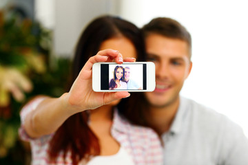 couple making selfie photo with smarphone. Focus on smartphone