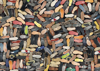 Background. A big bunch of different shoes, the soles.