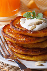 pumpkin pancakes with sour cream close-up on the table.