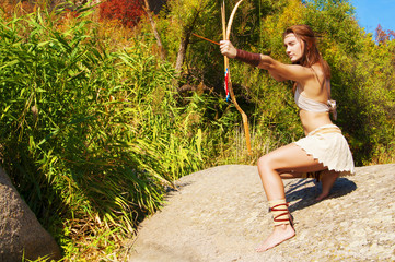 Primitive woman  holding a bow. Amazon woman