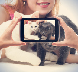 girl with two cats photographed on a smartphone