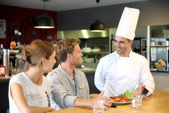 Young chef serving cooked dish to customers