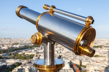 Shining telescope mounted on the railings of Eiffel Tower
