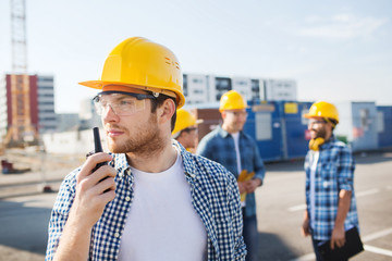 group of builders in hardhats with radio
