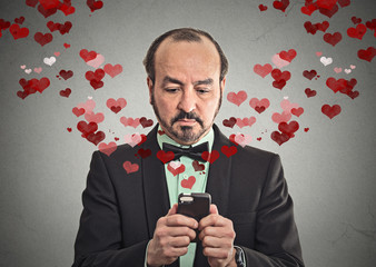 man sending love sms with mobile phone red heart flying away