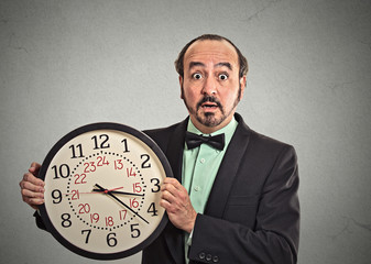 surprised businessman in suit holding wall clock grey background