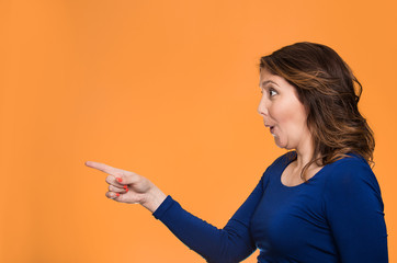 Surprised female pointing out at copy space, orange background