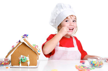 Cute Little Girl Decorating a Gingerbread House Tasting Candy