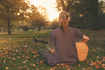 Woman sitting on grass playing guitar at sunset