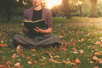 Woman reading in park at sunset