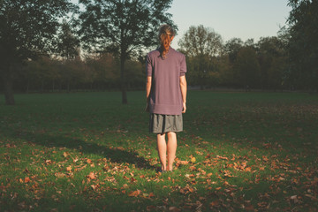 Woman standing on grass in evening