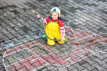 Funny little boy having fun with fire truck picture drawing with
