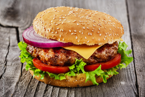Fototapete hamburger with grilled meat and cheese on a wooden surface