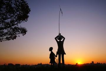 夕日と兄妹の像
