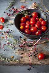 cherry tomatoes on bowl on rustic table with branches