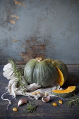 pumpkin cut in half on table with rosemary and garlic