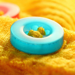 Colorful resin button on a yellow shirt.