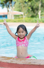 cute Asian girl enjoy to swimming at the pool