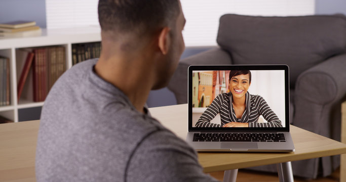 Two African friends video chatting on laptop
