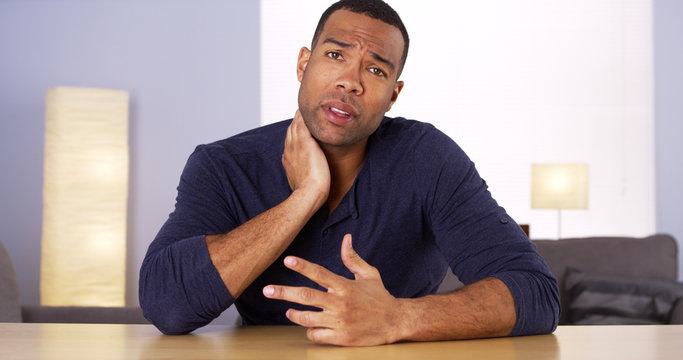 African man explaining neck pain to camera