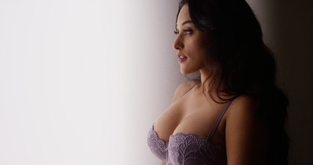 Sexy Mexican woman standing by window in lingerie