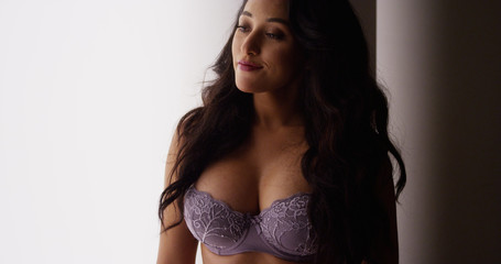 Mexican woman standing by window in lingerie