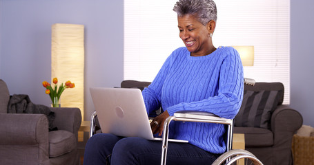 Mature African woman talking with friend on laptop