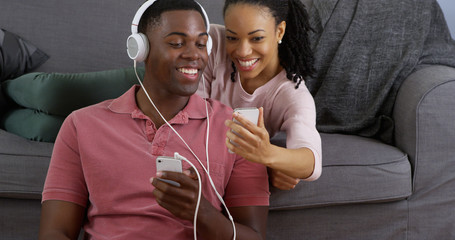 African American couple listening to music and taking picture with smart phones