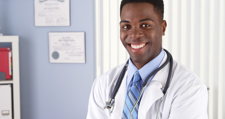Cheerful African American male doctor standing in his office