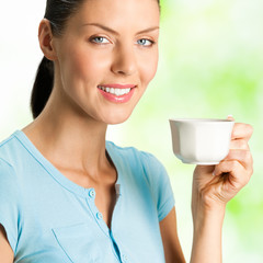 Young happy smiling woman drinking coffee, outdoors