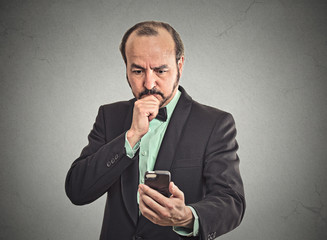 confused business man looking on smartphone thinking on reply
