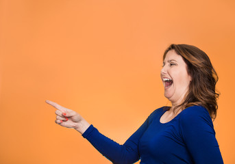 Side profile happy laughing woman pointing finger at something
